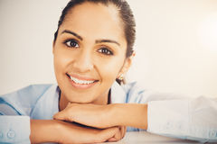 Closeup pretty Indian businesswoman smiling at desk in modern of Stock Images