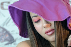 Closeup of pretty lady with makeup. Closeup of gorgeous fleshy lips and almond eyes with pink lipstick, long nails with france manicure wearing a purple floppy stock photo