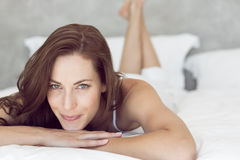 Closeup of a pretty smiling woman lying in bed Stock Photography