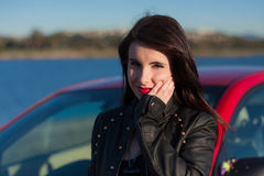 Closeup of pretty teen female wearing red lipstick in front of red car. Closeup of beautiful teen female, in afternoon sun, at the wheel of a red car, serious Stock Image