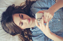 Closeup of pretty teenage girl lying in bed an looking at her mobile phone Stock Photos