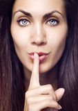 Closeup of pretty woman making silent gesture. Over isolated background Royalty Free Stock Images