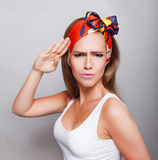 Closeup of a pretty woman saluting Stock Image