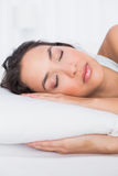 Closeup of a pretty woman sleeping with eyes closed in bed Stock Image