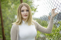 Closeup of pretty young woman standing near chain link fence Royalty Free Stock Image