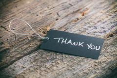 Closeup of pricing tag with twine. And Thank you text on wooden background Royalty Free Stock Images