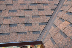 Closeup of problem areas for rain gutter waterproofing corner. New installed bitumen roof shingles Royalty Free Stock Photo