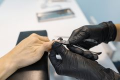 Closeup process of professional manicure. Manicurist woman hands in black gloves making manicure using professional tools. Nail stock photography