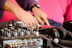 Closeup of producer's hands working with musical. Picture of producer adjusting volume with professional musical equipment and headphone. Closeup of male hands Stock Photo