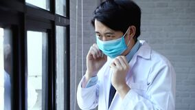 Closeup of professional Asian doctor wearing a surgical face mask for protection against coronavirus COVID-19 outbreak