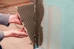 Closeup professional builder man's hand glues ceramic tile with adhesive in bathroom. Concept renovation repair, overhaul, royalty free stock images