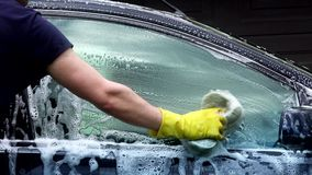 Closeup of professional car washer cleaning car window with soapy sponge. stock footage