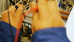 Electrician connects wires according to electrical circuit diagram. Closeup professional electrician connects wires using tool according to electrical circuit stock footage