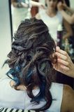 Closeup of a professional hairdresser`s hands doing a hairstyle in a beauty salon. Model of a brunette with long hair. The concep stock image