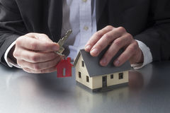 Closeup on professional hands holding a house key for home ownership Stock Photos