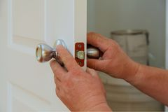 Closeup of a professional locksmith installing or repairing a new deadbolt lock. On a house door with the ine internal parts of the lock visible royalty free stock image