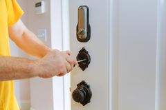 Closeup of a professional locksmith installing or repairing a new deadbolt lock. On a house door with the inside internal parts of the lock visible stock photography