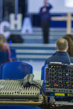 Closeup of Professional Mixing Console During Conference. With t. He Blurred Silhouette of  Spokesperson on a Background. Vertical Image Royalty Free Stock Images