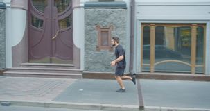 Closeup profile portrait of adult caucasian sporty male runner jogging down the street in the urban city outdoors stock video