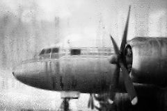Closeup of propeller driven plane. Closeup of large propeller driven plane seen through rain lashed window, gray background Stock Photo
