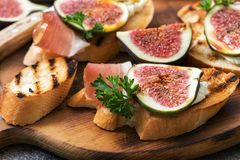 Closeup of prosciutto with figs on a cutting board. Selective focus. royalty free stock image