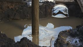 Prospecting pit metal pipe turns round in mud soil. Closeup prospecting pit metal pipe turns round in dirty puddle and extract important samples stock video footage