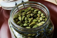 Closeup proto of glass jar full of green cardamom pods on brown plate.  royalty free stock photo