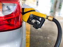 Closeup of pumping gasoline fuel in car at gas station pump. stock image