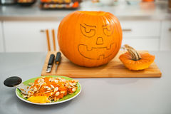 Closeup on pumpkin seeds with Jack-O-Lantern in background Stock Photography