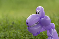 Closeup of purple balloon animal dinosaur in green grass of back Royalty Free Stock Image