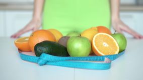 Keep Fit with Healthy Diet. Closeup of putting meter around fruits on white kitchen table, indoor shot with a woman in the background, keeping fit with healthy stock video footage