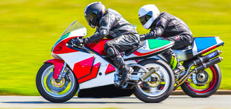 Closeup racing motorbikes. Closeup of racing motorbikes passing on track Royalty Free Stock Photography