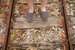 Closeup of railway and child`s feet on it. Top view royalty free stock photo