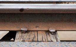 Closeup of the railway and metal peg. On the wooden sleeper of the old metal bridge which crossing the large river, Thailand royalty free stock photos