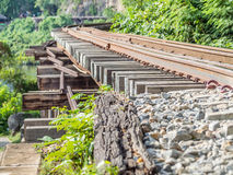 Closeup of railway train track on wooden bridge in the forest royalty free stock photos