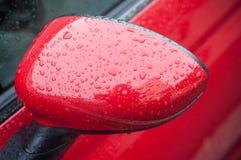 rain drops on red car mirror stock photos