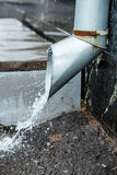 Closeup rainwater flow from the drainpipe installed on brick wall. Protection ftom heavy rains.. Stock Photos