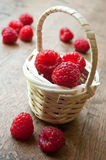 Closeup of raspberries  in a wooden basket. On wooden table background Royalty Free Stock Photo