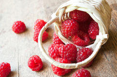 Closeup of raspberries  in a wooden basket. On wooden table background Stock Photos