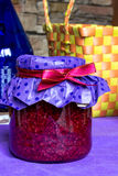 Closeup raspberry jam-jar decorated  ribbon,  straw basket, eco kitchen. Closeup photo of sweet raspberry jam-jar, with red  ribbon and craft paper, strow busket Royalty Free Stock Photos