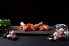 Closeup of raw chicken thighs with garlic, paprika, salt and pepper mixture on a dark background. Around the cutting Stock Photos