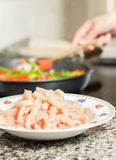Closeup of raw chiken dish and female cooking in a pan in the ba Stock Photo