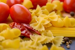 Closeup raw pasta and tomatoes. Italian food concept Royalty Free Stock Photo
