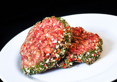 Closeup of raw red hamburgers on white plate. Isolated on black Stock Images