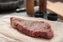 closeup raw seasoned new york steak on concrete countertop background