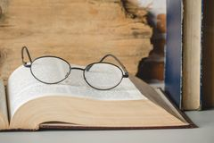 Closeup of reading glasses with open book on table.  royalty free stock photo
