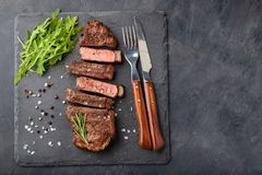 Closeup ready to eat steak new York beef breeds of black Angus with herbs, garlic and butter on a stone Board. The. Finished dish for dinner on a dark stone royalty free stock photography