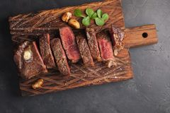 Closeup ready to eat steak new York beef breeds of black Angus with herbs, garlic and butter on a wooden Board. The finished dish royalty free stock images