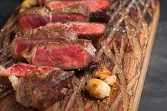 Closeup ready to eat steak new York beef breeds of black Angus with herbs, garlic and butter on a wooden Board. The finished dish. For dinner on a dark stone Stock Image