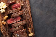 Closeup ready to eat steak new York beef breeds of black Angus with herbs, garlic and butter on a wooden Board. The finished dish stock photo